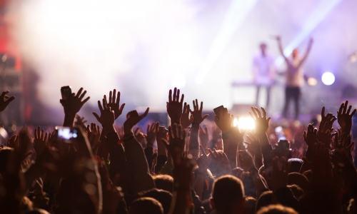Crowd with raised hands attending a concert